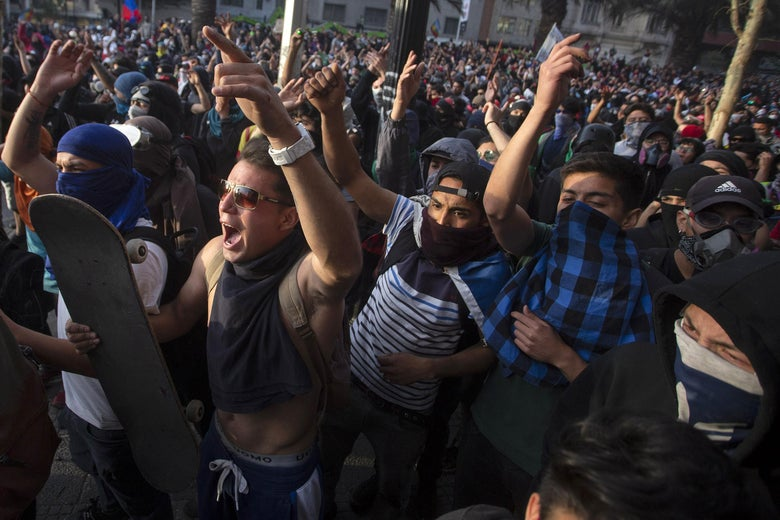 Demonstrators clash with riot police during protests against the government economic policies, in the surroundings of La Moneda presidential palace in Santiago, on October 29, 2019. - Chilean President Sebastian Pinera unveiled a major cabinet reshuffle on the eve as he battles to find a response to more than a week of street protests that have left at least 20 people dead. (Photo by CLAUDIO REYES / AFP) (Photo by CLAUDIO REYES/AFP via Getty Images)