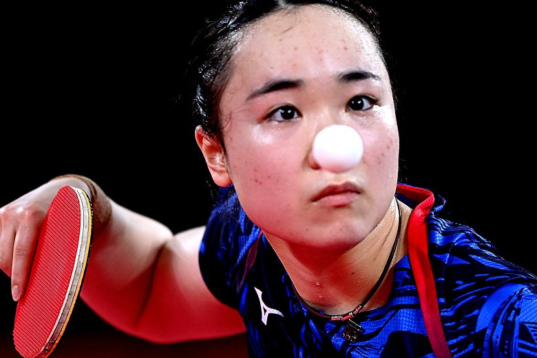 A table tennis player stares intently as she holds her paddle. The white ping pong ball is centered on her face like a clown nose.