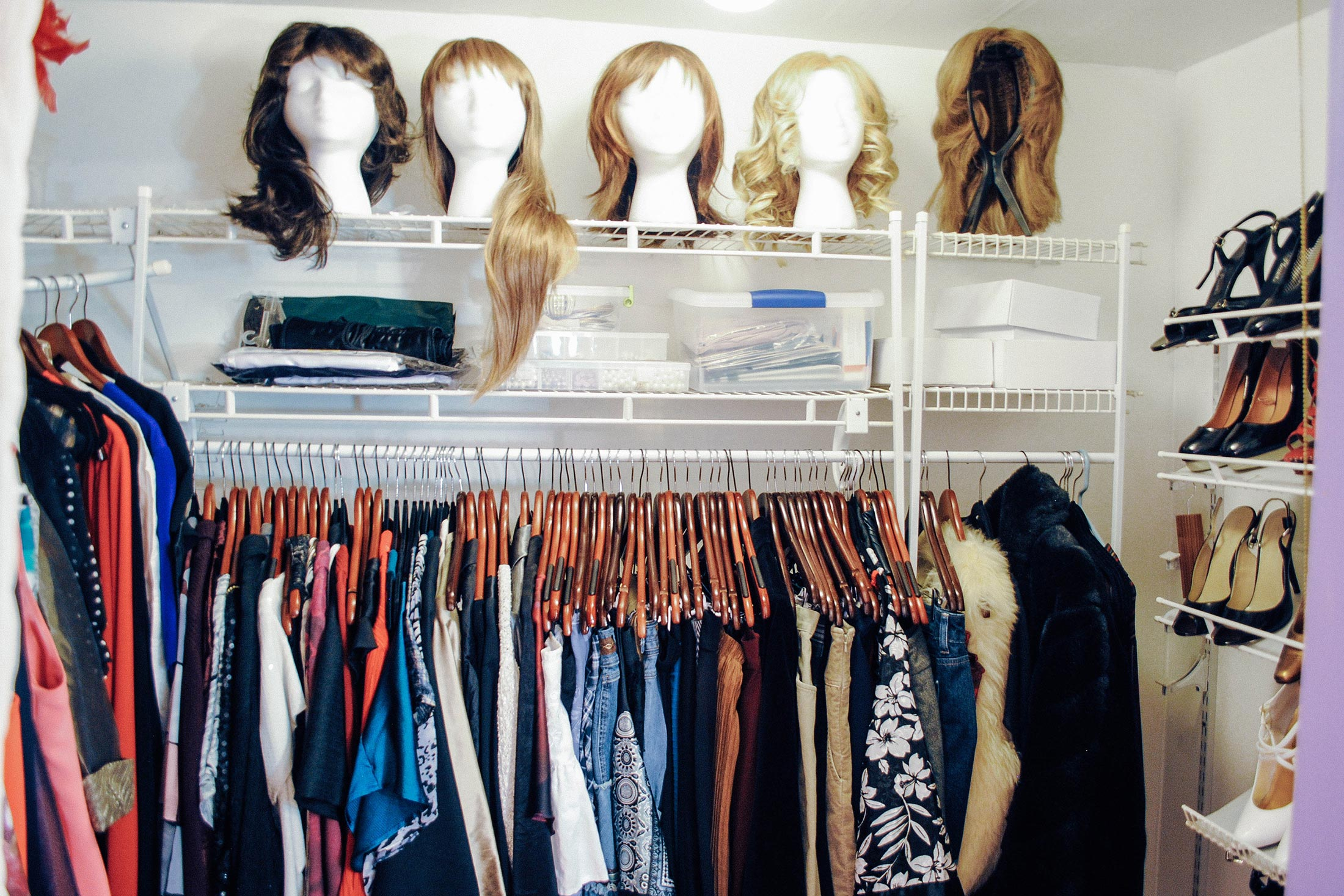 A closet containing women's clothing, wigs, and shoes.