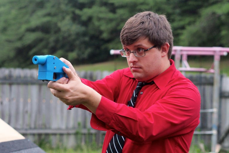 Software engineer Travis Lerol takes aim with an unloaded Liberator handgun in the backyard of his home on July 11, 2013.
