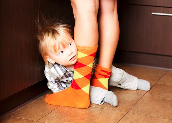 Boy hiding behind parent's legs