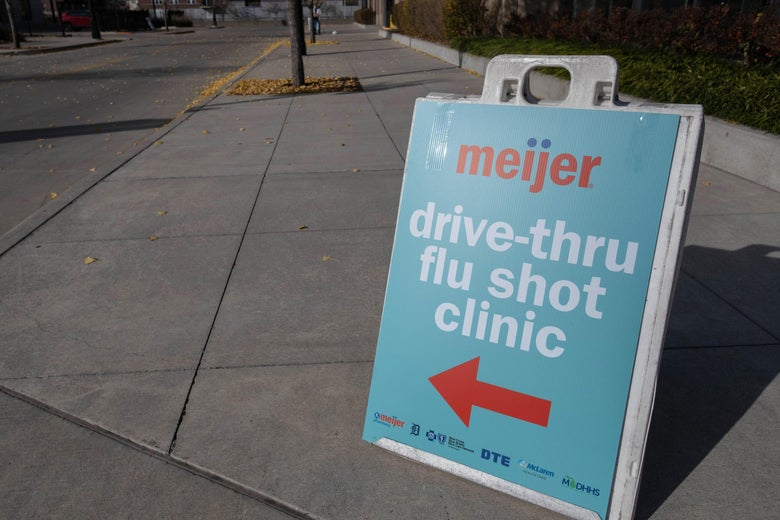 """A sign that says, """"Meijer drive-thru flu shot clinic,"""" featuring a red arrow pointing toward the clinic."""