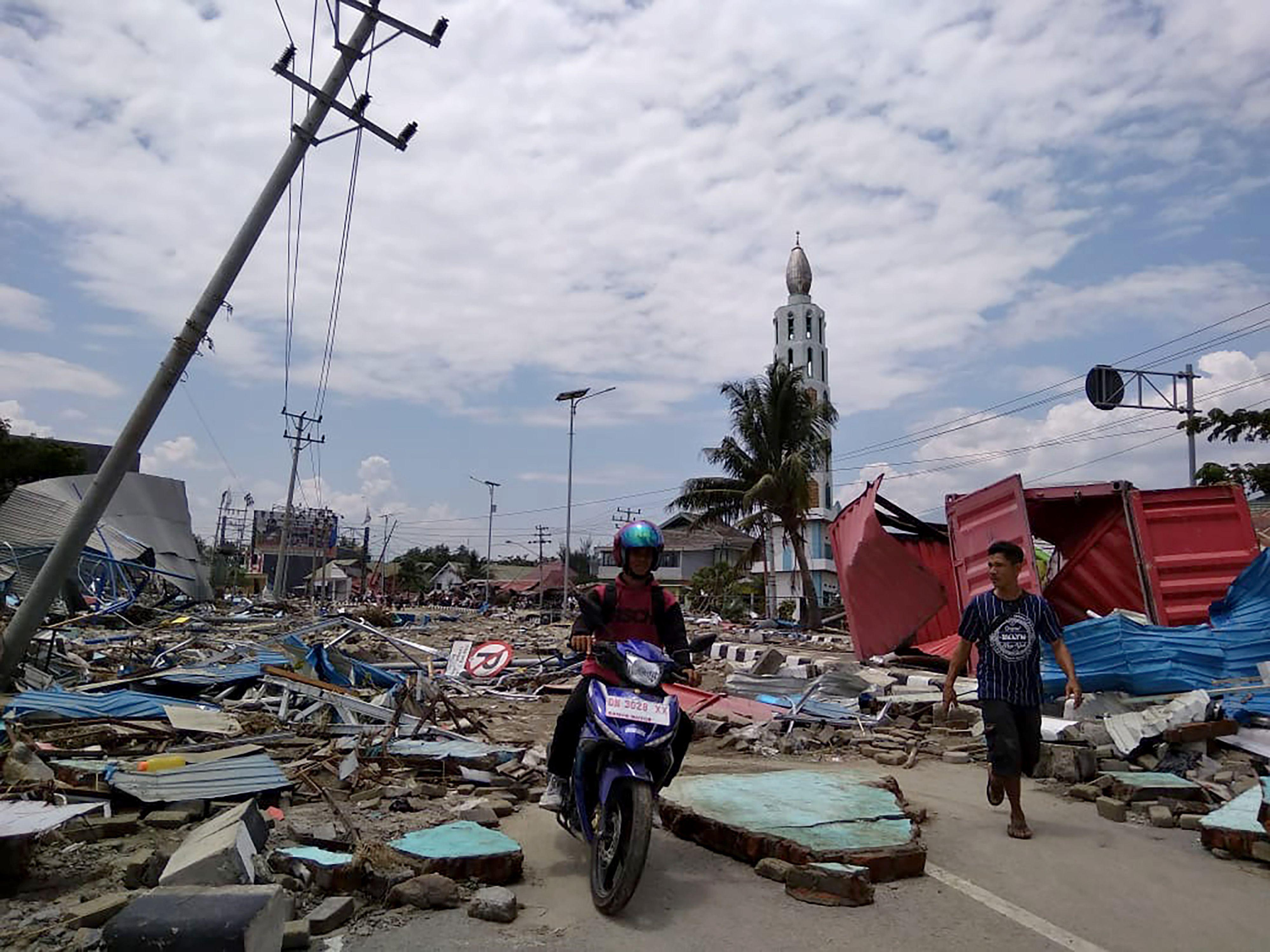 Residents make their way along a street full of debris after an earthquake and tsunami hit Palu.