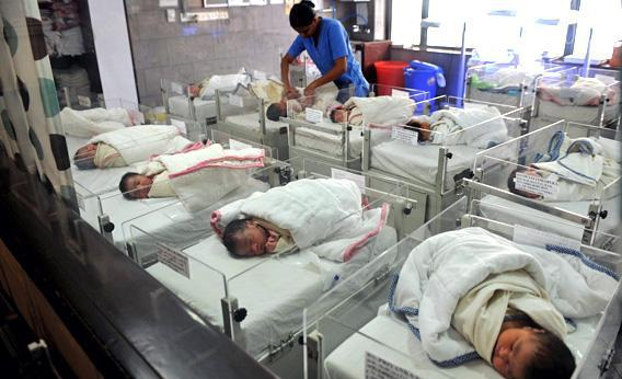 An Indian nurse cares for new born babies in a nursery at a maternity hospital in Kolkata in September 2010.