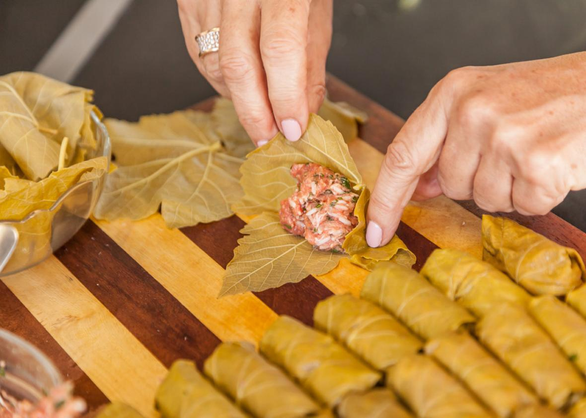Rolling the meat and rice filling into vine leaves for yaprakes de oja parra kon arros.