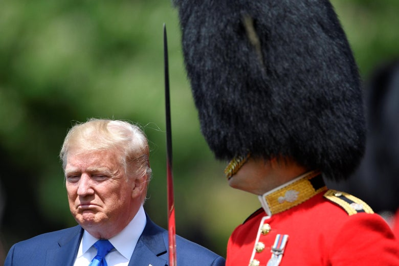 A frowning Trump stands next to a member of the Queen's Guard.