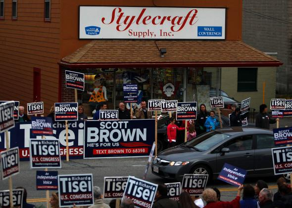 A car is flanked by campaign signs for Sen. Scott Brown and congressional candidate Richard Tisei outside of a campaign rally in Wakefield, Mass., on Nov. 1, 2012.