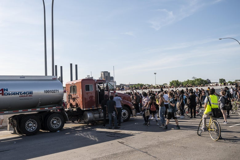 People react after a tanker truck drove into a crowd peacefully protesting the death of George Floyd on the I-35W bridge over the Mississippi River on May 31, 2020 in Minneapolis, Minnesota.
