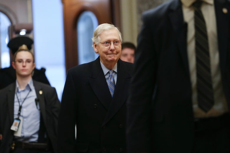 Mitch McConnell walks with aides behind him.
