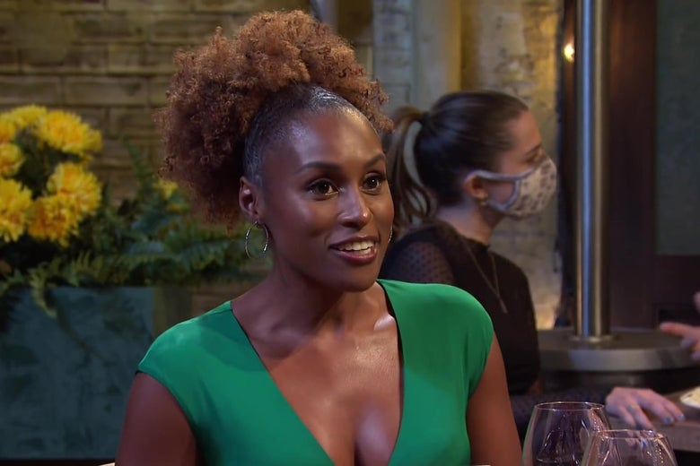 Issa Rae, in a green dress, sitting at an outdoor table in a sketch from Saturday Night Live.