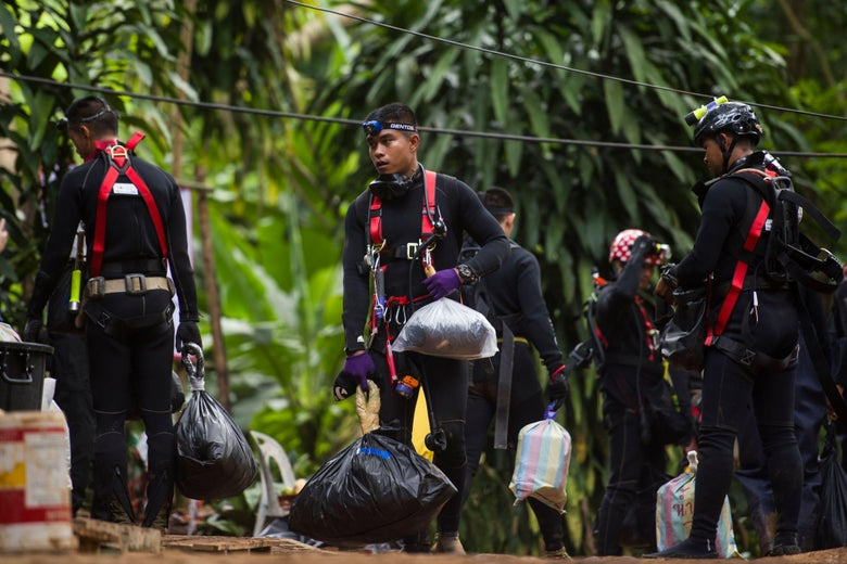 Thai divers carry supplies as rescue operations continue for 12 boys and their coach trapped at Tham Luang cave at Khun Nam Nang Non Forest Park in the Mae Sai district of Chiang Rai province on July 5, 2018. - Thai rescuers vowed to take a 'no risk' approach to freeing 12 boys and their football coach from a flooded cave, as fresh video emerged on July 4 showing the team in good spirits following their astonishing discovery nine days after going missing. (Photo by YE AUNG THU / AFP)        (Photo credit should read YE AUNG THU/AFP/Getty Images)