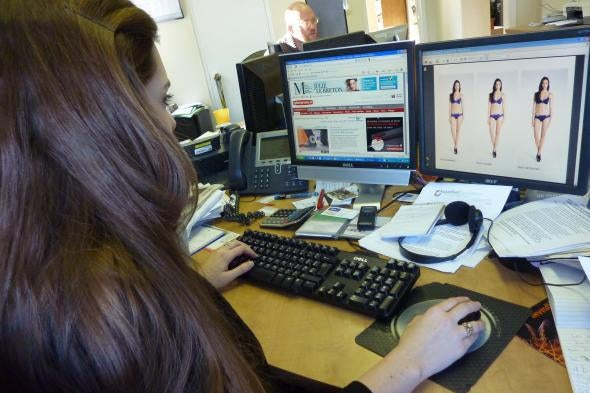 Woman sitting at a computer altering an image of a woman in a bikini in a software program on the screen