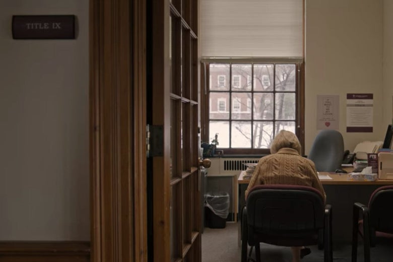 A door opens into an office in a college building, where Joan sits in a chair in front of a desk.
