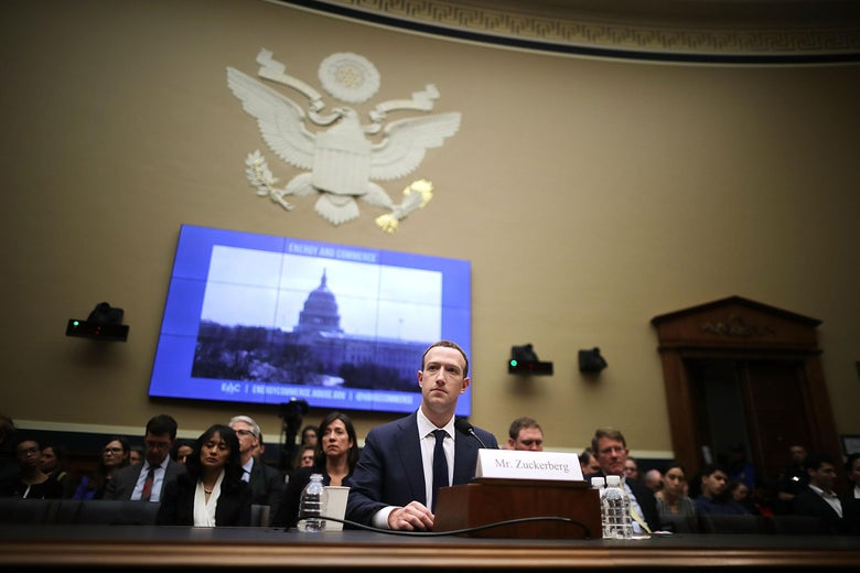 Zuckerberg sits at a table in a large room. Behind him are an audience of watchers, a screen showing an image of the Capital Building, and the Great Seal of the U.S.