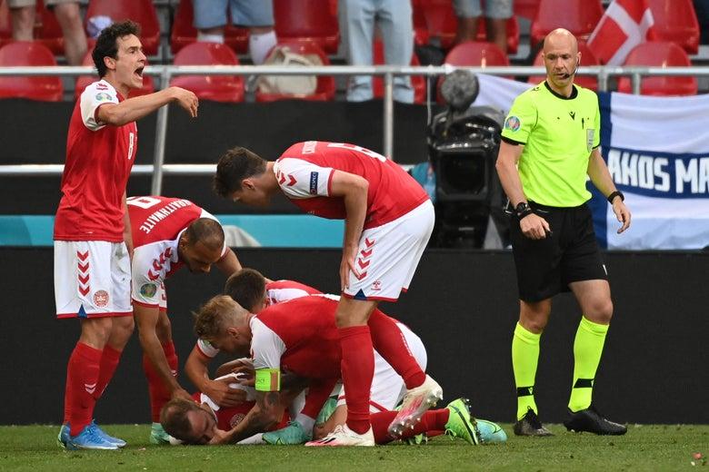 Denmark players help Denmark's midfielder Christian Eriksen after he collapsed during the UEFA EURO 2020 Group B football match between Denmark and Finland at the Parken Stadium in Copenhagen on June 12, 2021.