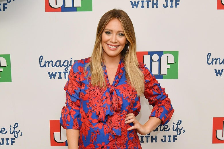 Hilary Duff standing in front of a sign for Jif Peanut Butter.