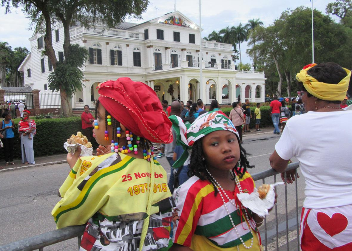 Children wait for the military parade in front of Suriname's presidential palace.
