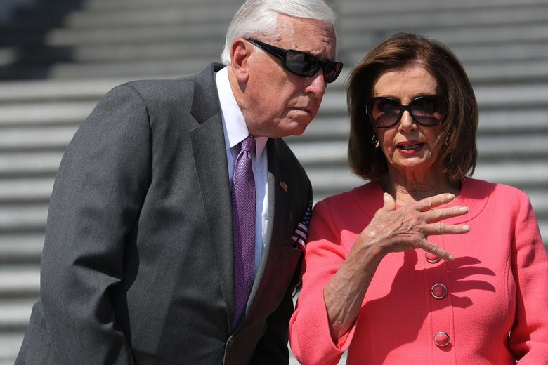 Hoyer, wearing sunglasses, leans over to listen to Pelosi, who is also wearing sunglasses.