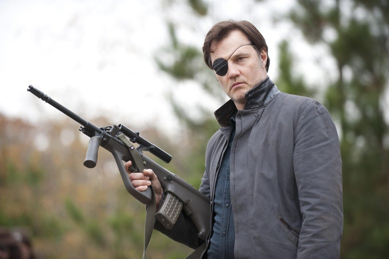 A man in an eye patch holds a rifle.