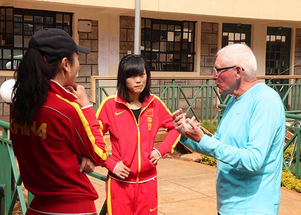 Coach Renato Canova talks with athlete Wang Mei via interpreter Anna Lin.