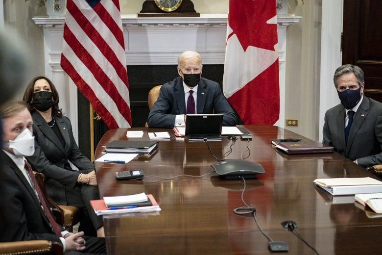 Sullivan, Harris, Biden, and Blinken seated around a conference table, wearing masks