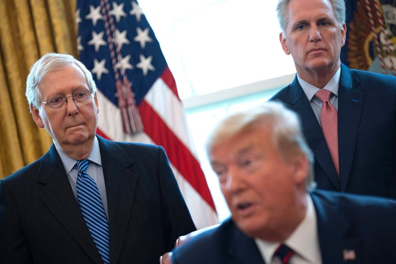 Mitch McConnell and Kevin McCarthy stand behind and look at Donald Trump.