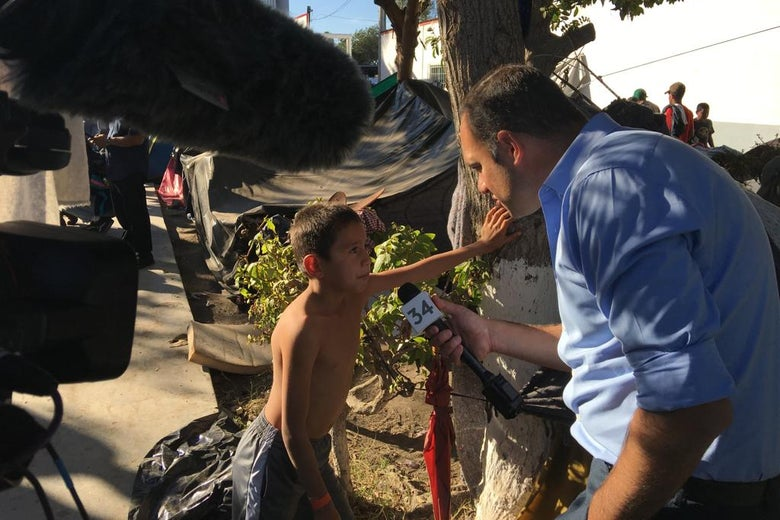 The reporter holds a microphone up to a child leaning against a tree. In the background, a row of makeshift tents in the Tijuana migrant camp.
