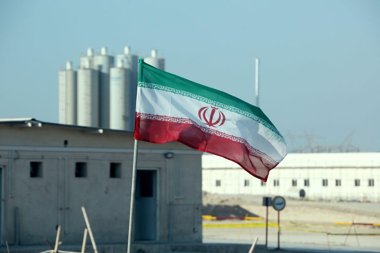 An Iranian flag flying in front of a nuclear power plant.