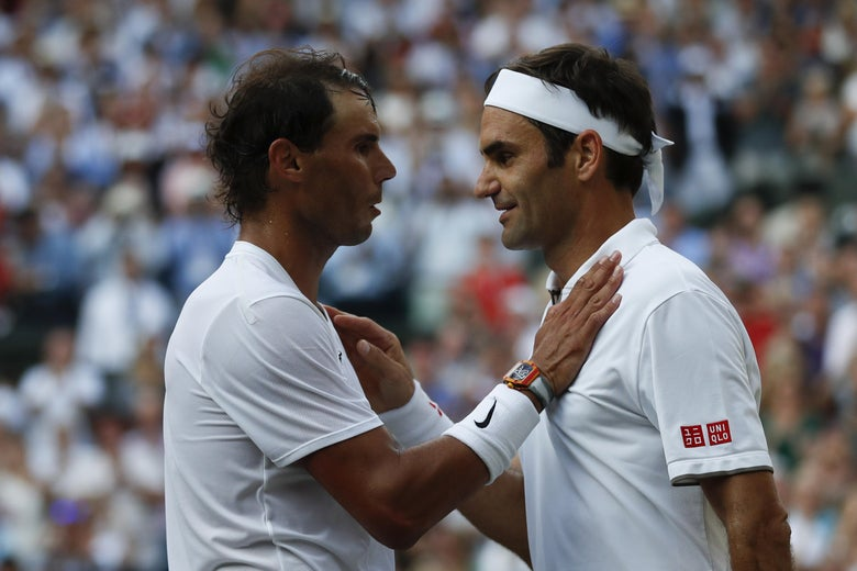 Roger Federer and Rafael Nadal embrace at the net.