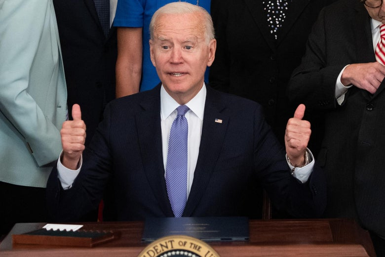 Joe Biden sits at a desk and flashes two thumbs up as people stand behind him.
