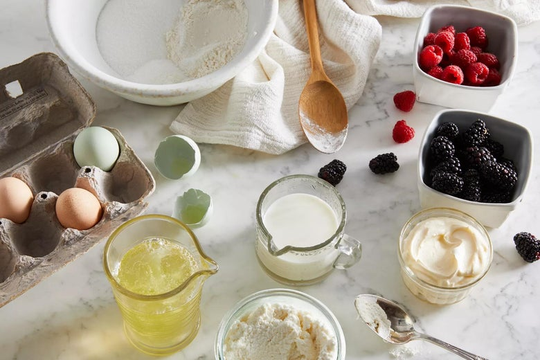 On a marble countertop: eggs, melted butter, flour, cream, blackberries, raspberries, and a mixing bowl.