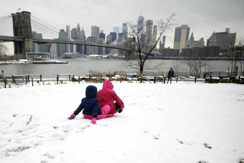 Two girls ride a sled on a snow-covered hill in New York.