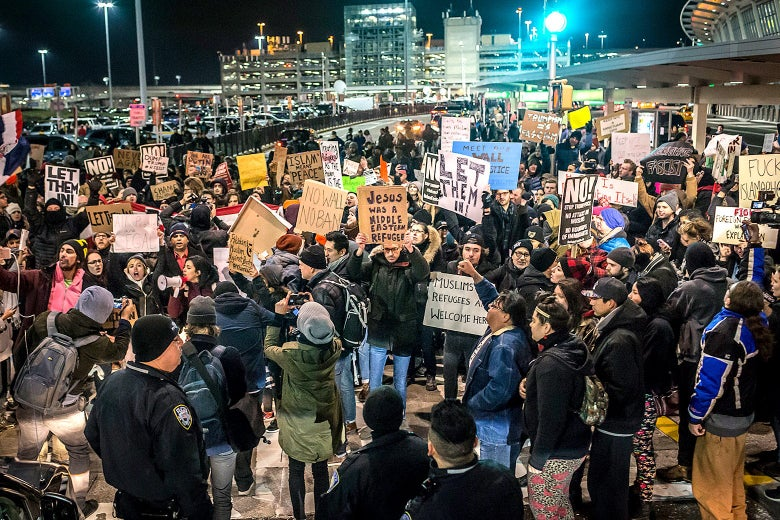 People hold up signs against the Muslim ban outside the terminal at night.