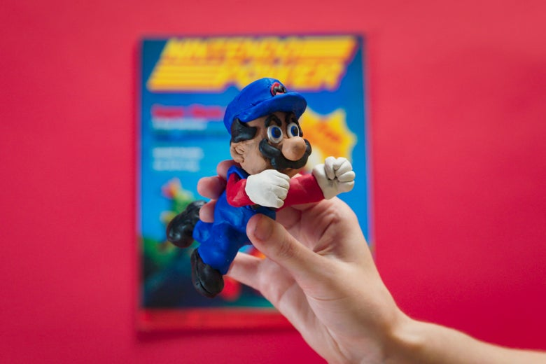A Mario figurine in front of an old copy of Nintendo Power