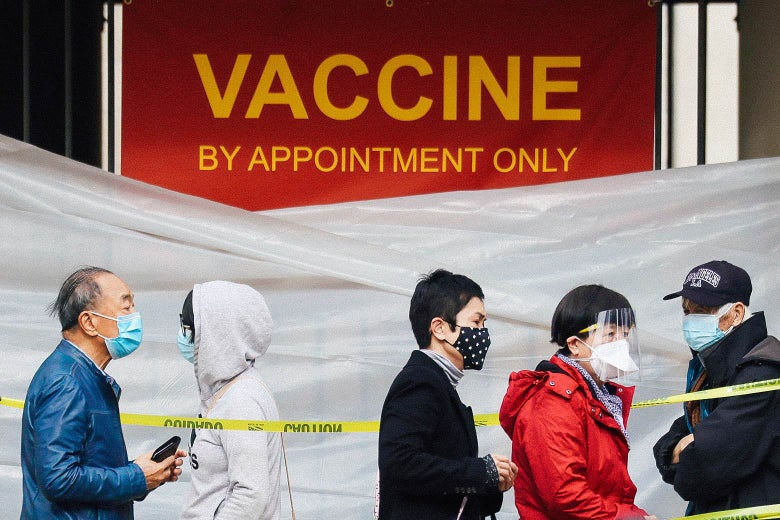 "People stand in a line demarcated by yellow caution tape, in front of a sign that says ""VACCINE BY APPOINTMENT ONLY"""