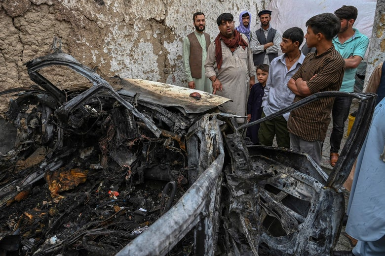 Afghan residents and family members of the victims gather next to a damaged vehicle inside a house, day after a US drone airstrike in Kabul on August 30, 2021. (Photo by WAKIL KOHSAR / AFP) (Photo by WAKIL KOHSAR/AFP via Getty Images)
