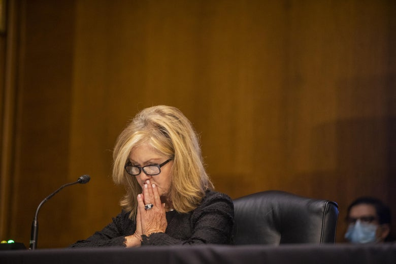 Blackburn seated in a Senate hearing room, looking at her desk and holding her palms together in front of her mouth