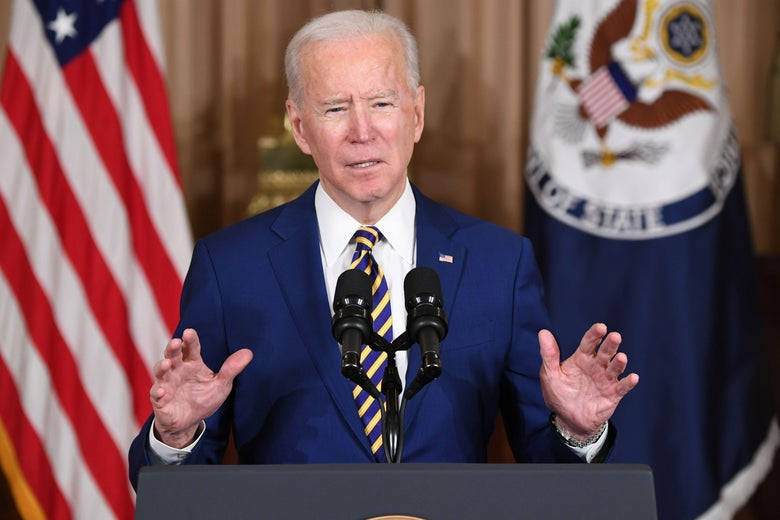 Biden speaks at a podium with an American flag and a State Department flag behind him
