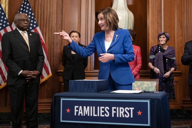 "Pelosi points to her right and smiles in front of a table with a banner reading ""Families First."""