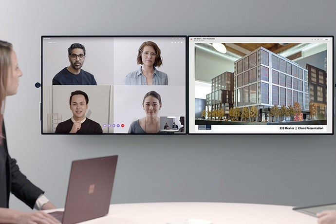 A woman uses the Surface Hub 2 to teleconference with four people as she makes a presentation about a building.