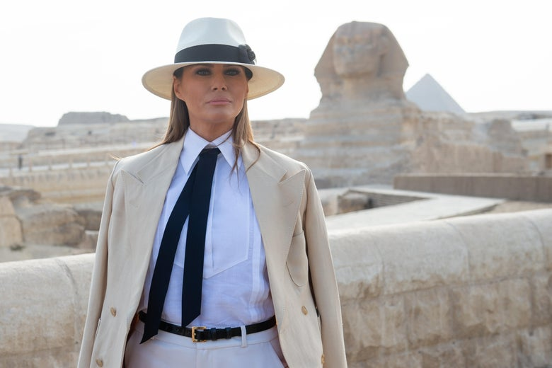 Melania, dressed in white and linen, poses for the camera in front of the Sphinx.