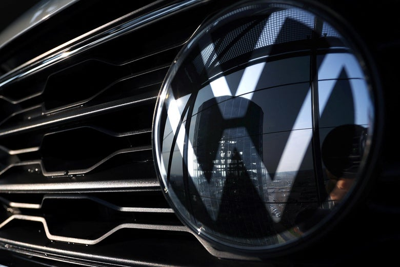 A VW logo reflecting a building is seen on the grille of a car.