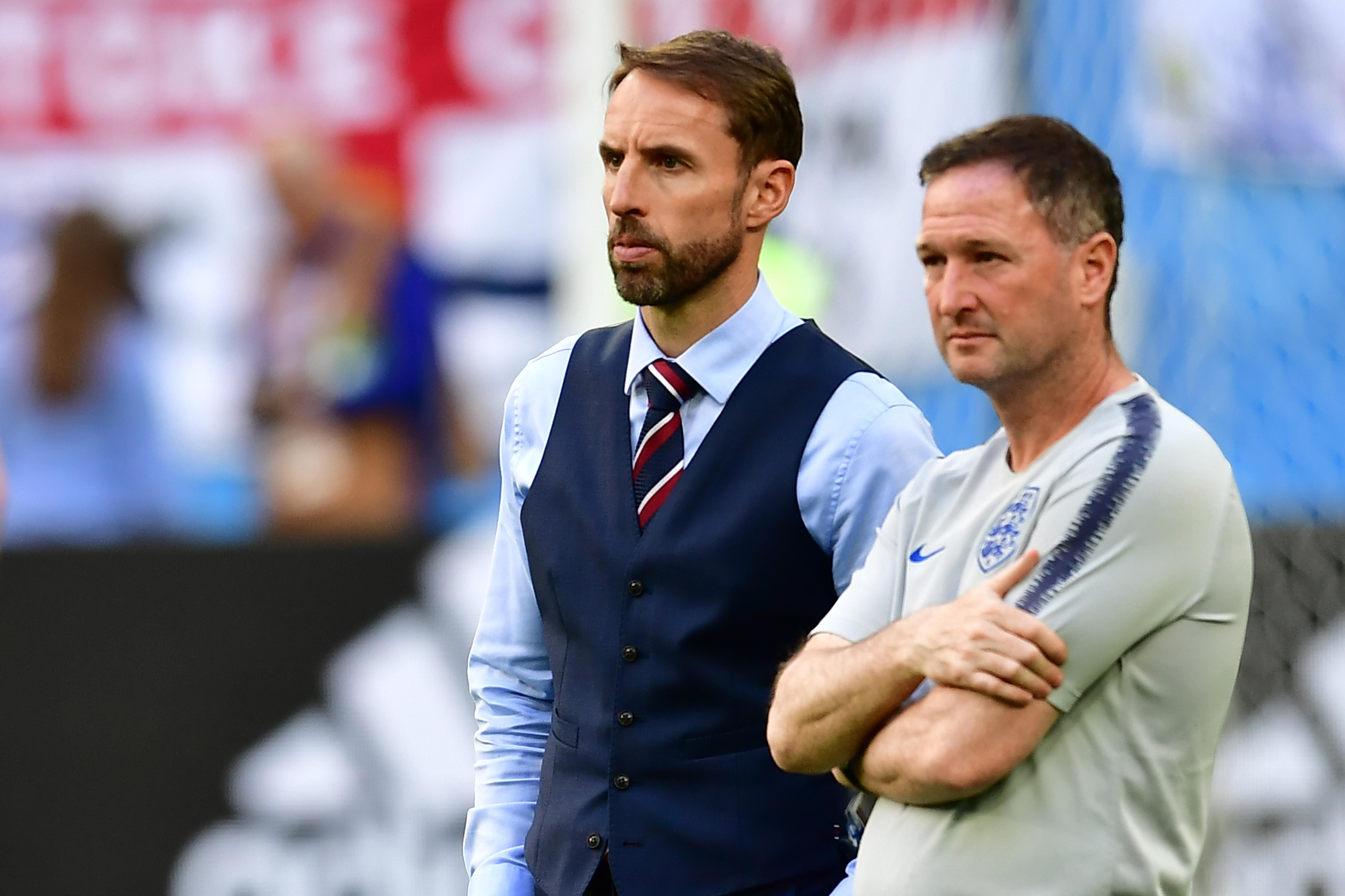 England's coach Gareth Southgate, wearing a vest, and an assistant react to Belgium's victory.