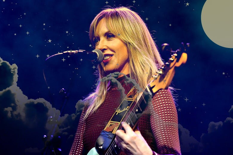 A woman with long blonde hair stands in front of a microphone. She is holding a guitar with a black strap that says Fender on it across her chest. Her shirt is reddish purple with mesh sleeves. Behind her is an illustration of a night sky, with gold stars, a bright white moon, and gray-blue clouds.