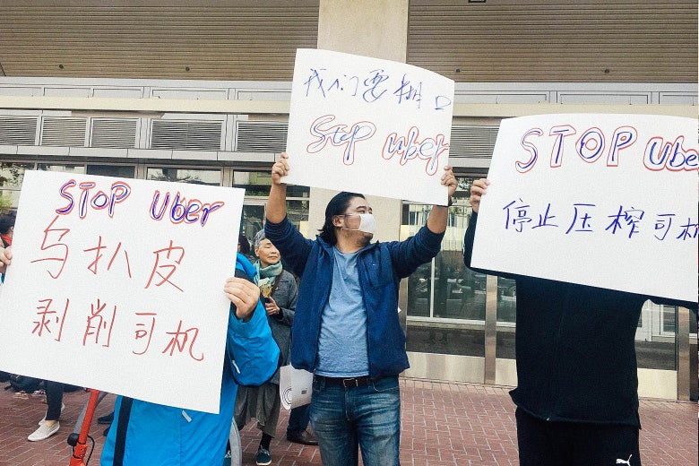 Protesters holding anti-Uber signs in Chinese.