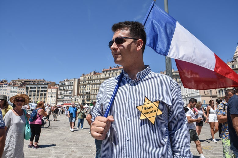 """Man in sunglasses holding a French flag and wearing a yellow star reading """"sans vaccin."""""""