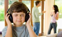 Boy listening to headphones while parents fight.