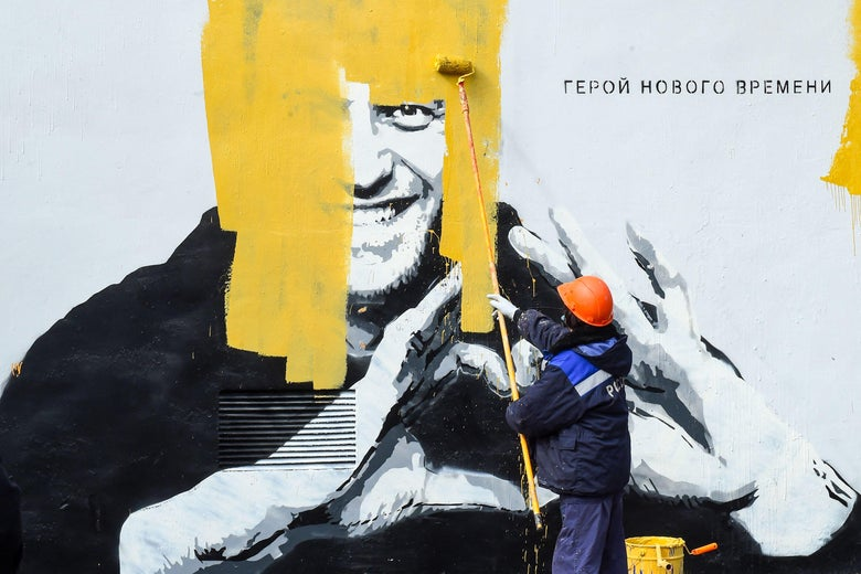 """A worker paints over graffiti of jailed Kremlin critic Alexei Navalny in Saint Petersburg on April 28, 2021. The inscription reads: """"The hero of the new times"""". (Photo by Olga MALTSEVA / AFP) (Photo by OLGA MALTSEVA/AFP via Getty Images)"""