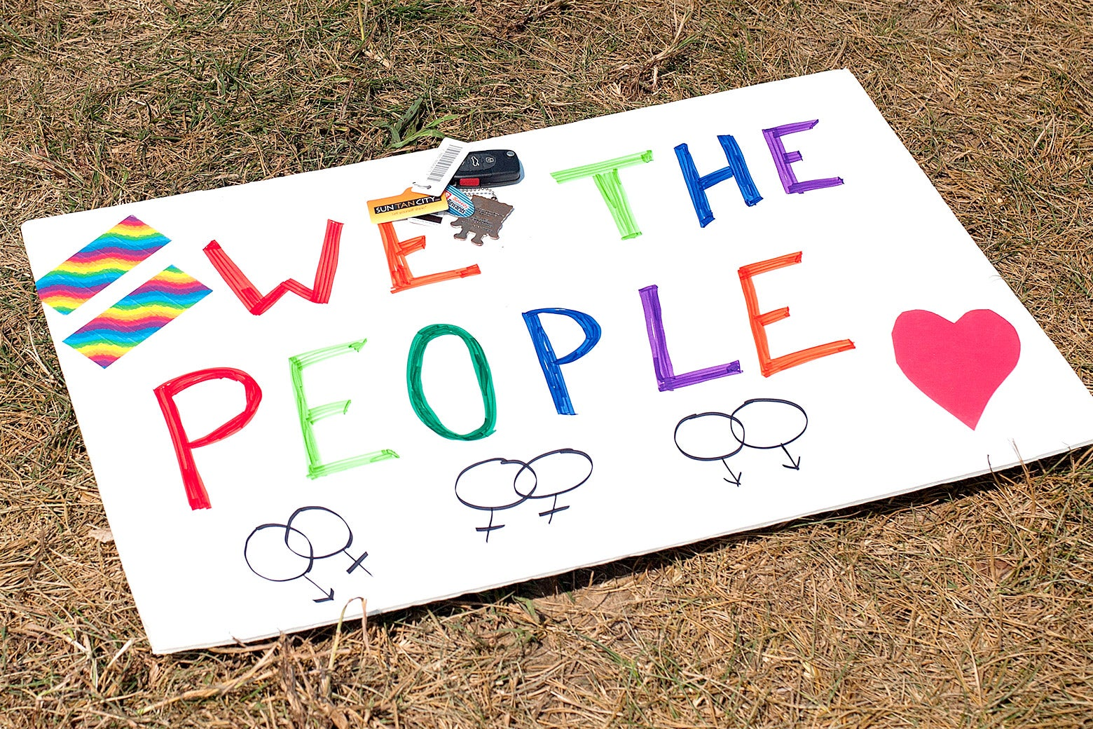 """A sign supporting same-sex marriage (""""We the People"""" with rainbow-colored lettering, a heart, and intertwined female symbols) lies on the ground in front of the Rowan County Courthouse on Sep. 2, 2015, in Morehead, Kentucky."""