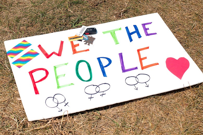 "A sign supporting same-sex marriage (""We the People"" with rainbow-colored lettering, a heart, and intertwined female symbols) lies on the ground in front of the Rowan County Courthouse on Sep. 2, 2015, in Morehead, Kentucky."